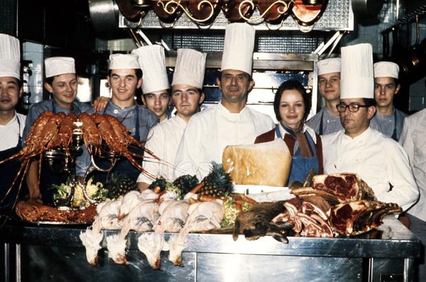 O chef Paul Bocuse (centro, de chapéu mais alto) e sua equipe rodeada por animais em restaurante em Lyon, França, em 1973
