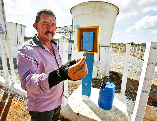 Secretário de Agricultura de Riacho das Almas, Naelson Beserra, segura ficha usada no 'orelhão' da água, parte de sistema que extrai e dessalinizar água do solo