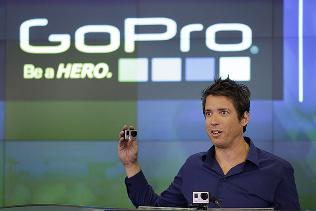 FILE - In this Thursday, June 26, 2014, file photo, GoPro CEO Nick Woodman celebrates his company's IPO at the Nasdaq MarketSite in New York. GoPro is cutting staff and expects a sharp decline in fourth-quarter revenue after facing weak demand for cameras during the 2017 holiday season. As part of the restructuring plan, Woodman will cut his 2018 cash compensation to $1. It was $800,000 in 2016. (AP Photo/Seth Wenig, File) ORG XMIT: NYBZ113