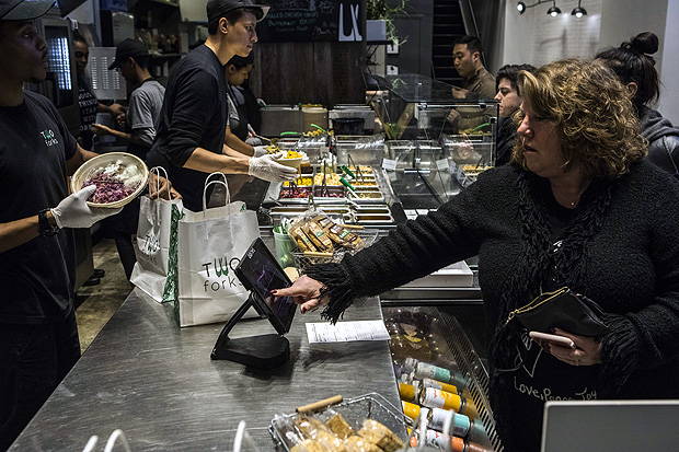 A patron pays with a credit or debit card at a Two Forks restaurant that does not accept cash, in New York, Dec. 20, 2017. A growing number of New York businesses do not accept U.S. currency, to the consternation of some and the indifference of others. (Hiroko Masuike/The New York Times) ORG XMIT: XNYT79