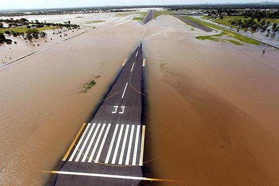 Enchente cobre a pista do aeroporto de Rockhampton, em Queensland; cidade desapareceu sob as águas
