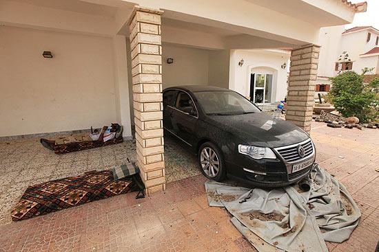 Carro de luxo é visto estacionado em casa danificada pelos combates entre rebeldes e gaddafistas em Sirte