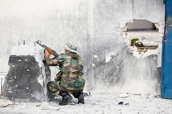 Soldado rebelde se protege durante combate com forças leais a Gaddafi na cidade de Sirte