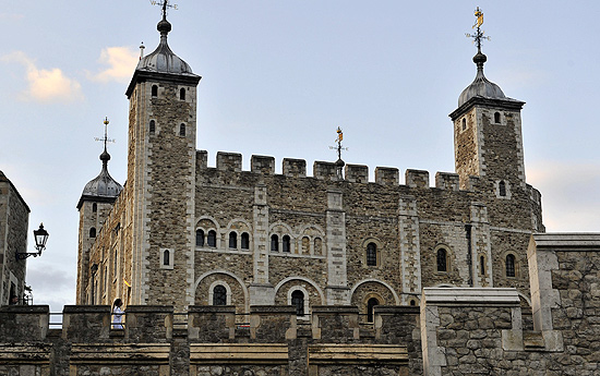 A atleta britânica Kelly Holmes corre com a tocha olímpica em frente à Torre de Londres, em julho