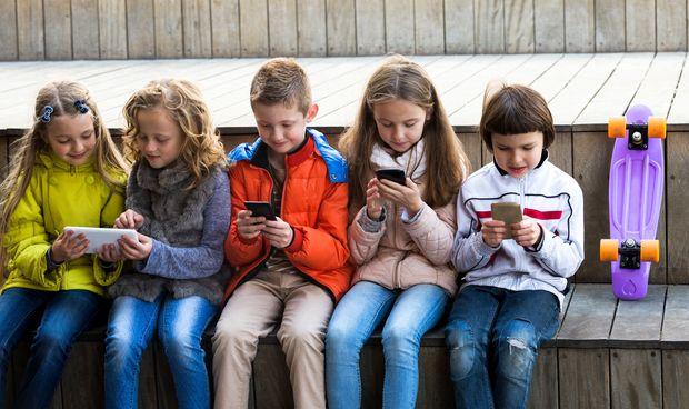 Crianças usando celulares e tablets