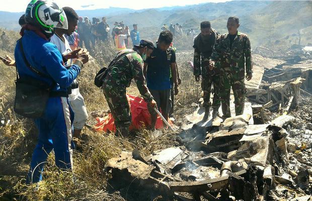 Soldados examinam destroços de avião caído na Indonésia