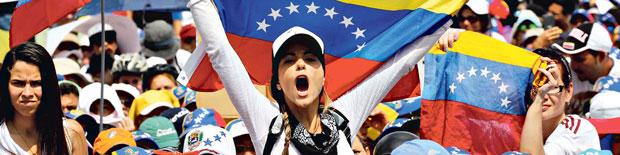Mulheres levantam bandeiras em um protesto feminino no último sábado (6) em Caracas