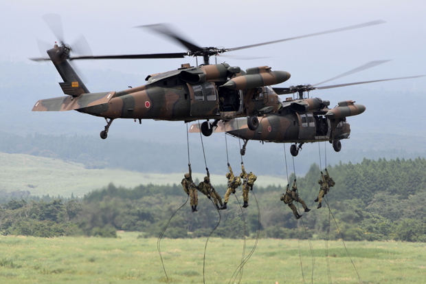 (FILES) This file photo taken on August 24, 2017 shows Japan Ground Self-Defense Force troops descending from helicopters during an annual live-fire exercise at the Higashi-Fuji firing range in Gotemba, at the foot of Mount Fuji in Shizuoka prefecture. Japan's defence ministry said on August 31 it will request its largest-ever annual budget, just days after nuclear-armed North Korea fired a rocket over the country in a provocation that drew global condemnation. / AFP PHOTO / Toshifumi KITAMURA