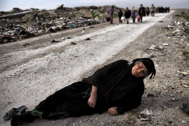 "-- AFP PICTURES OF THE YEAR 2017 -- An Iraqi woman lies on the ground as civilians flee Mosul while Iraqi forces advance inside the city during fighting against Islamic State group's fighters on March 8, 2017. Supported by US-led air strikes, the forces have made steady progress in their battle to seize Iraq's second city from the Islamic State group, announcing the recapture of two more areas. Hundreds of thousands of civilians are believed to still be trapped under jihadist rule in the Old City, where Abu Bakr al-Baghdadi proclaimed a ""caliphate"" in his only public appearance in July 2014. / AFP PHOTO / ARIS MESSINIS ORG XMIT: ARIS3059"
