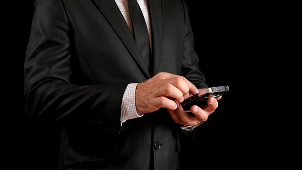 Concept, digital online life and social networks. A businessman in a black business suit with a tie uses his smartphone to view his accounts. Expressive shot, a man in a dark room, holding a stylish phone. 4k.