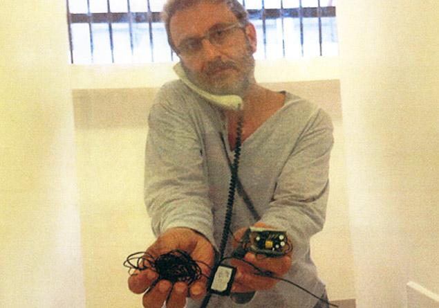 O doleiro Alberto Youssef mostra equipamento que ele diz ter achado dentro da cela, na carceragem da Polícia Federal, em Curitiba (PR)
