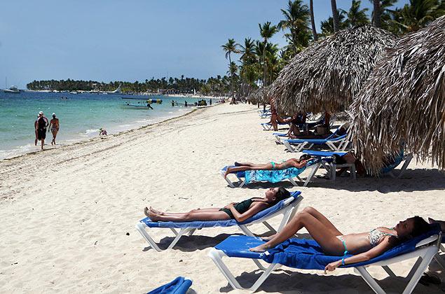 Turistas em praia de Punta Cana, bom destino para quem quer ficar longe do clima de Copa