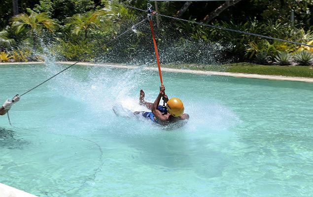 Visitante em tirolesa no Arraial d'Ajuda Eco Parque, que, além da estrutura com piscinas de ondas, dá acesso à praia do Mucugê