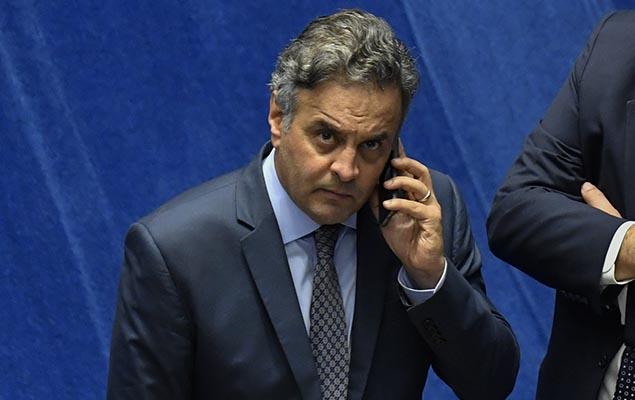 Senador Aécio Neves (PSDB) fala ao telefone durante sessão no Senado, em Brasília, na noite desta quarta-feira