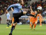 O craque uruguaio Forlan, em impedimento, domina a bola