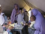 Sobreviventes de alagamentos no Paquistão aguardam atendimento médico em acampamento para desabrigados em Nowshera