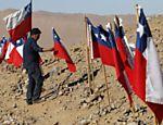 Parente de trabalhador soterrado há 19 dias em mina do Chile estende bandeira do país; resgate pode demorar meses <a href=