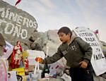 Menino acende vela em altar dedicado aos mineiros presos na jazida San José, no Chile <a href=