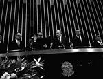 Em 1985, com a mão direita levantada, dirigindo-se ao plenário do Congresso, José Sarney lê o juramento e toma posse como presidente da República