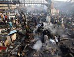 Moradores calculam os estragos após um incêndio de grandes proporções destruir a favela Gareeb Nagar, em Mumbai (Índia) <a href=