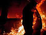 Bombeiro passa por um veículo em chamas em Tijuana. De acordo com policiais, pistoleiros não identificados, estavam fugindo depois de matarem dois homens
