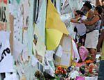 Pessoas deixam flores e cartazes para as vítimas do massacre de Realengo <a href=