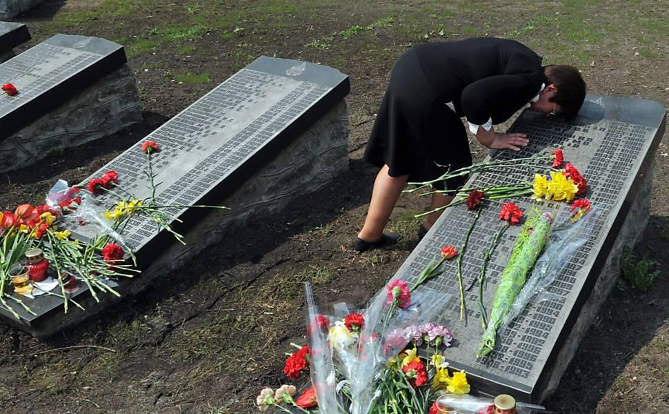 Mulher presta homenagem às vítimas em cemitério de Kiev, na Ucrânia