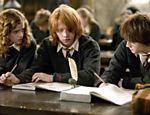 Novamente em Hogwarts, Hermione (Emma Watson), Ron (Rupert Grint)e Harry (Daniel Radcliffe) tramam durante a aula em cena do filme
