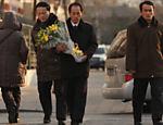 Homem leva flores à embaixada norte-coreana em Pequim, em luto pela morte do ditador Kim Jong-il <a href=