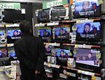 Homem assiste às notícias sobre a morte do ditador norte-coreano em loja de eletrônicos em Tóquio, no Japão <a href=