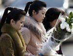 Mulheres norte-coreanas levam flores à embaixada norte-coreana em Pequim, em luto pela morte de Kim Jong-il <a href=