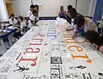 Profissionais da equipe da artista Laura Tajes auxilam a montagem do mural colocado no pátio da escola <a href=