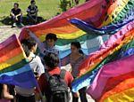 Grupo de jovens carregam bandeiras do arco-íris na praça de Armas de Assunção, no Paraguai
