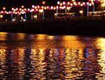 Iluminação de final de ano na cidade do Recife; a cidade cortada por rios, encontram neles um espelho para o espetáculo <a href=