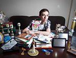 O mestrando em comunicacao João Paulo Hergesel, 20, com seus livros e prêmios que ganhou em concursos de literatura