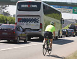 Ciclista pedala no canteiro da rodovia dos Imigrantes durante congestionamento no sentido litoral