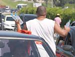 Homem vende água em meio aos carros na rodovia dos Imigrantes durante congestionamento no sentido litoral