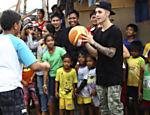 Justin Bieber joga basquete com jovens sobreviventes do tufão Haiyan em Palo, nas Filipinas