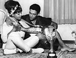 O jogador de futebol Mané Garrincha e a cantora Elza Soares posam para foto com faixa de campeão da Copa de 1958 e a taça Jules Rimet (Foto: Acervo UH/Folhapress)