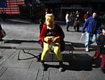 Homem vestido de Homer Simpsons natalino tira foto com turistas em Nova York, em novembro deste ano