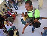 Assistente social carrega criança da minoria Rohingya em Lapang, na Indonésia <a href=