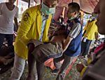 Médicos da Indonésia carregam migrante de Bangladesh para o setor médico do alojamento em Langsa, uma vila de pescadores
