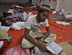 Imigrante lê livro sagrado do islamismo em abrigo temporário em Langsa, na Indonésia