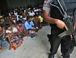 Policial da Indonésia vigia abrigo para refugiados durante visita de embaixador de Bangladesh ao local