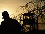 Soldado americano caminha próximo à cerca de arame farpado do Campo X-Ray, em Guantánamo