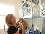 Luisa Mell pega no colo outro cachorro que está na clínica, à espera de adoção