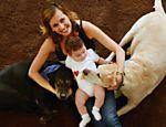 Luisa com o filho, Enzo, e os cachorros Gisely e Marley, na sala de casa