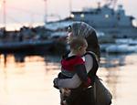 Mulher síria carrega bebê em direção ao navio Eleftherios Venizelos, que se tornou um centro improvisado de cadastramento de refugiados na ilha de Kos, na Grécia