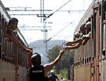 Policial serve água para refugiados na Macedônia que viajam em direção à Sérvia