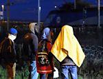 Imigrantes em frente a cercas na cidade de Calais, França, onde muitos tentam usar o túnel do Canal da Mancha para chegar ao Reino Unido